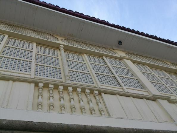 Sliding windows and balustrades of this bahay-na-bato convent that is attached to the church